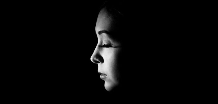 woman looking sad with closed eyes against a dark background to illustrate toxic shame
