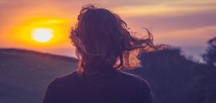 young woman looking out at the sunset with hair blowing in the wind