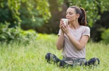 a woman sitting on grass holding and smelling a takeaway coffee - illustrating the 54321 grounding technique