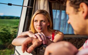 couple looking out across countryside from their camper van