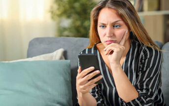 confused young woman staring at her phone wondering why he won't text first