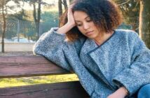 young woman sitting on bench looking like she just doesn't care about anything anymore