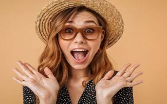 woman who looks excited with hands in the air illustrating an intense person