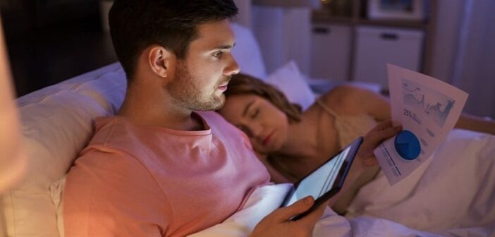 workaholic husband looking at tablet computer and paperwork in bed whilst his wife sleeps