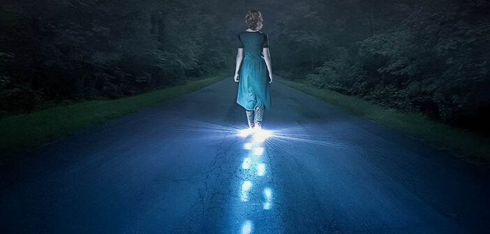person walking in darkness with glowing footsteps of light - illustrating narcissistic abuse recovery
