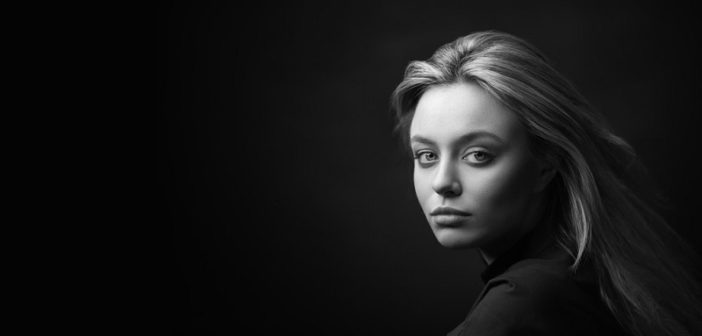 woman with serious face against a black background illustrating being unhappy