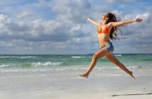 woman jumping up and celebrating on a beach illustrating winning at life