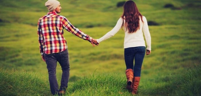 couple holding hands walking through field to illustrate companionship in a relationship