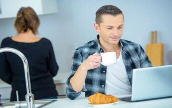 man going through his morning routine drinking coffee and checking his emails on his laptop