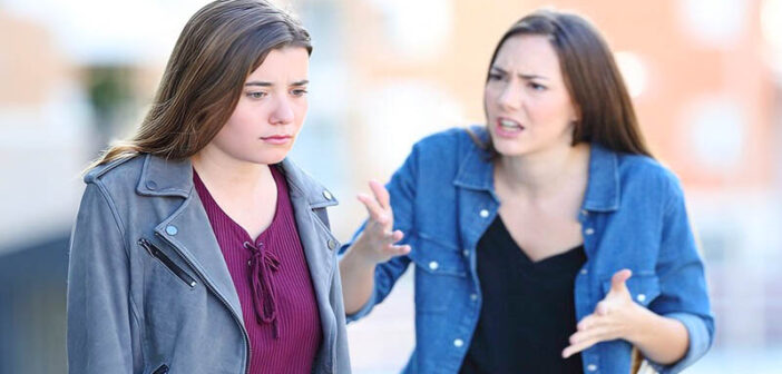 young woman being disrespectful to her friend in the street