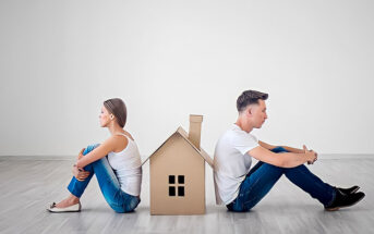 couple sitting facing away from each other with cardboard house between them - illustrating an in-house trial separation