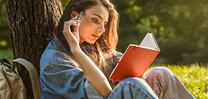 woman sitting under a tree writing her life purpose statement in a notepad