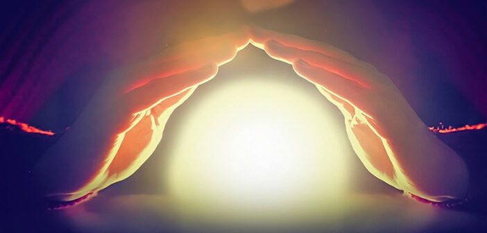 hands covering glowing orb of light - illustrating protection from negative energy