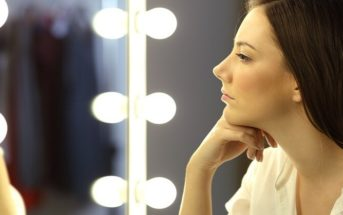 woman looking at her reflection in a mirror to illustrate self-reflection questions