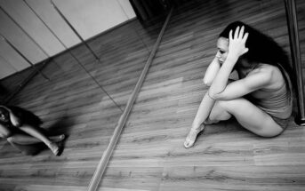 woman in dance studio sitting on floor looking sad - illustrating trying to stay positive in a negative world