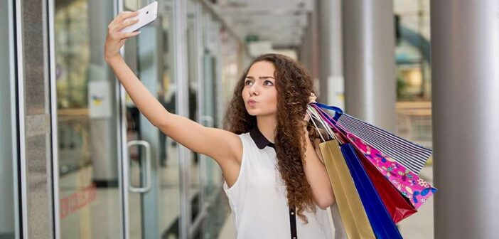 young woman taking selfie with shopping bags whilst pouting - signs of a try hard