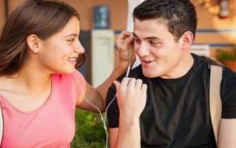 smiling young man and woman sharing headphone illustrating chemistry between people