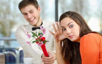 girl looking awkwardly away from a guy with flowers who is coming on too strong