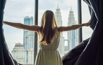 woman opening curtains with city view - illustrating doing something with your life