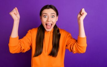 woman with excited face with clenched fists in the air illustrating how to be enthusiastic