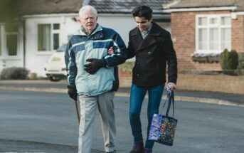 young man helping an elderly man across the road - illustrating random acts of kindness