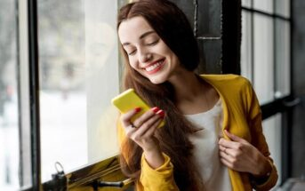 smiling woman looking at phone - illustrating texting too much before a first date