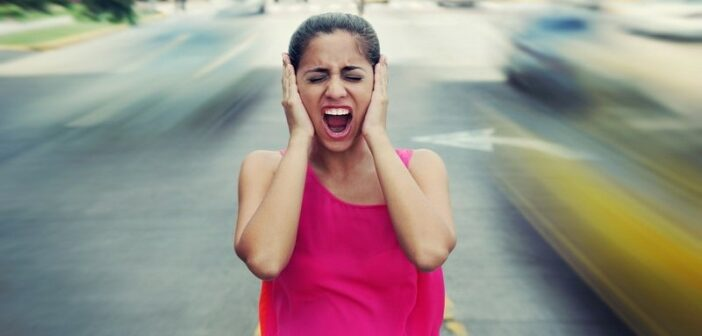 woman screaming holding her ears as traffic drives past - illustrating a world that is going crazy