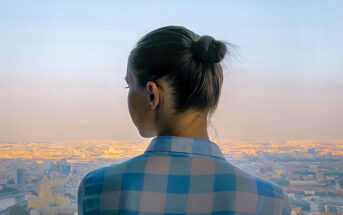 young woman looking out over city feeling like she has no direction in life