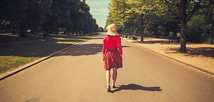 woman in red walking down an empty street - illustrating a life transition