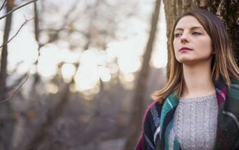 pensive looking woman standing in a forest thinking she needs a change in life