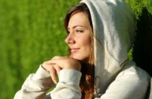 a young woman sitting with face toward the sun with a little smile on her face after rebooting her life
