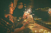 young woman lighting sparklers in a jar - illustrating appreciating what you have