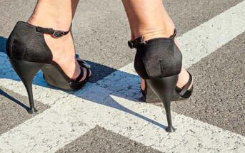 closeup of woman's feet in high heels standing on white lines going in opposite directions - illustrating a crossroads in life