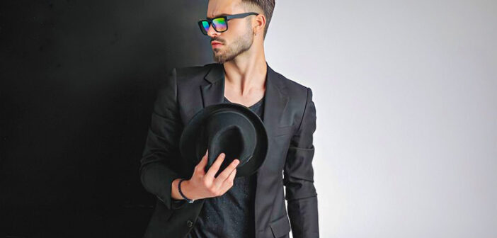 arrogant looking young man dressed in black with sunglasses and a hat - illustrating a bad boy