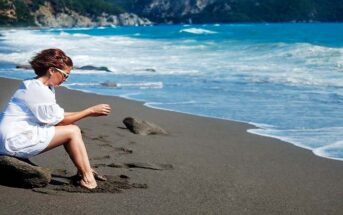 woman sitting on a rock at the beach with feet in the sand - illustrating slowing down