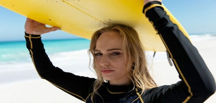 young woman in wetsuit carrying a surfboard above her head - illustrating an exciting and interesting life