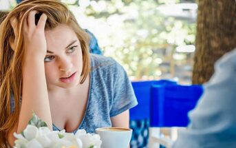 woman looking frustrated with her boyfriend at a cafe - illustrating a love-hate relationship