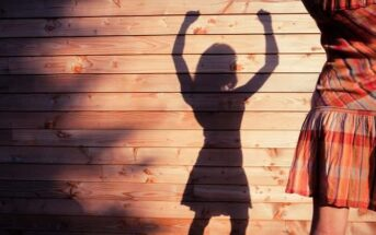 woman casting shadow with raised arms to signify changing her life
