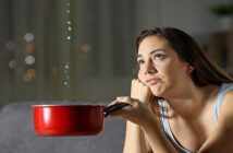 woman holding pan under leaking water from her ceiling - illustrating when nothing goes right