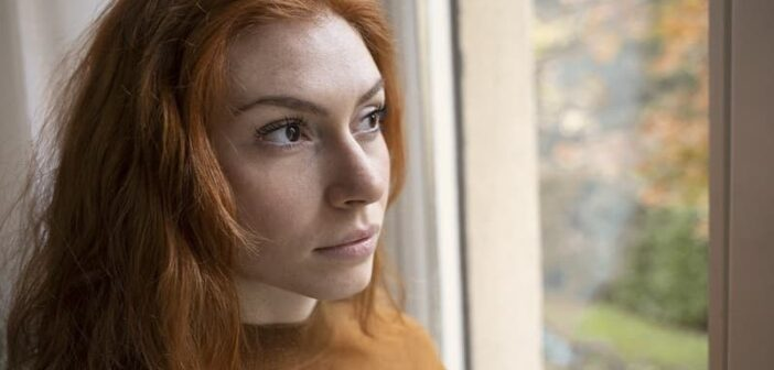 pensive young woman looking out of a window illustrating a private person