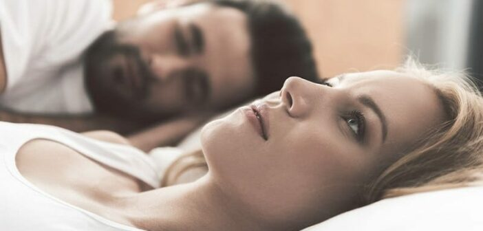 woman lying in bed next to partner unhappy in the relationship, but she still loves him