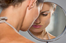 "upset woman looking at herself in the mirror asking ""why doesn't he want me?"""
