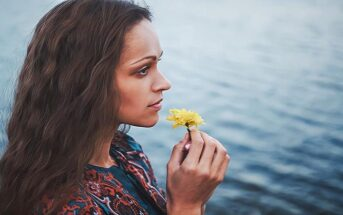 young woman smelling flower but she can't enjoy it or anything
