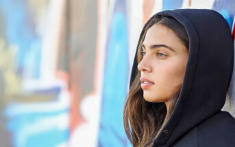 young woman leaning against a wall not knowing how she is feeling