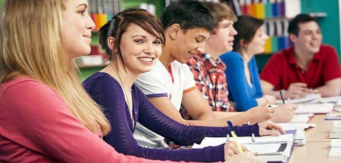 smiling teenage school children in class