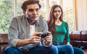 wife looking upset because she's not getting any attention from her husband who is playing video games