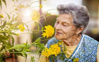 wise elderly woman smelling a flower - illustrating good advice for life