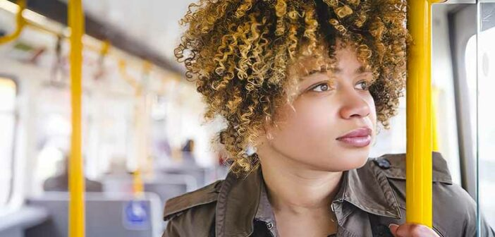 woman standing on a bus looking out of the window wondering what her calling in life is