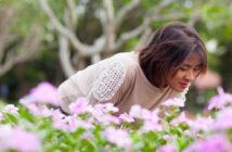 woman smelling some pink flowers - illustrating improving your quality of life