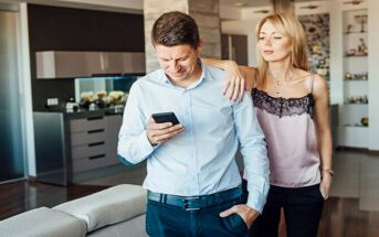 jealous wife looking over husband's shoulder at his phone